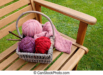 Basket of knitting and yarns on a bench - Craft basket of...