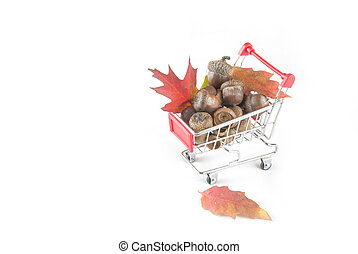 A red shopping cart full of fall foliage and acorn.