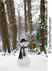 Freezing snowman standing in the park wearing a hat