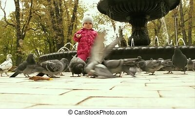 a small girl is watching the birds