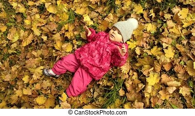 a small girl on yellow leaves - a small girl is lying on...