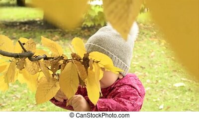 A baby is playing by the tree