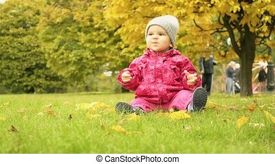 a small girl sitting on the ground