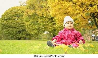 a small girl sitting in the park
