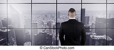 Businessman Looking Out the Window to New York City