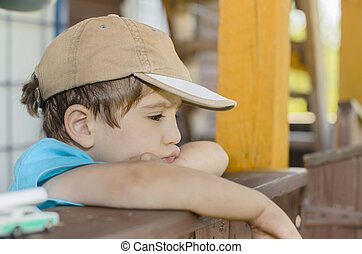 Child's glance - A wistful child on his porch