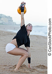 Model Kettlebell beach training - Model using fitness...