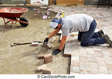 Man laying down paver - Young man laying down paver as part...