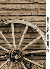 old wagon wheel side by wooden wall