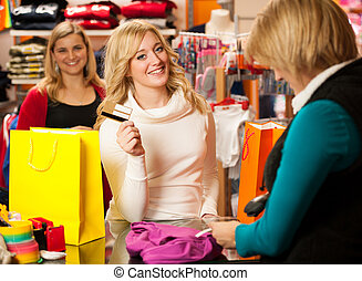 Cute young woman paying after succesfull purchase with...