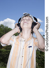 teenager in ear-phones - The teenager in ear-phones listens...