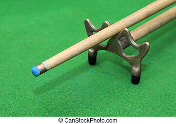 snooker cue with rest isolated on green background