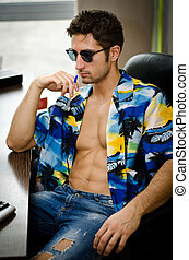 Handsome young man with open shirt at his office desk