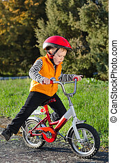 Cute young boy riding his bike - Cute young boy in a...
