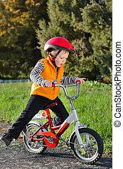 Cute young boy riding his bike - Cute young boy in a...