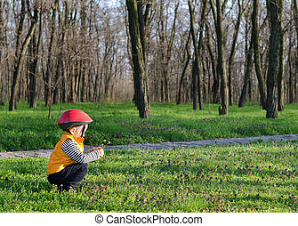 Little boy playing outdoors in woodland crouching down on...