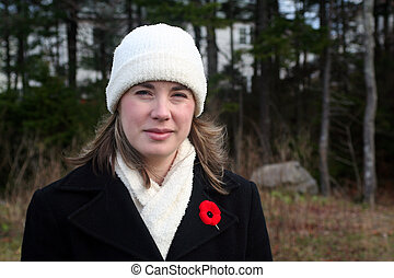 Remembrance - A beautiful young woman wearing a red poppy on...