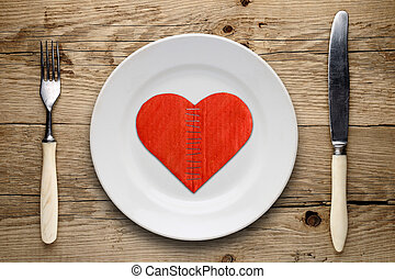 Broken cardboard heart on plate on wooden background