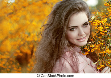 Autumn Girl Portrait. Happy smiling Woman over yellow leaves in the autumn park. Outdoor photo.