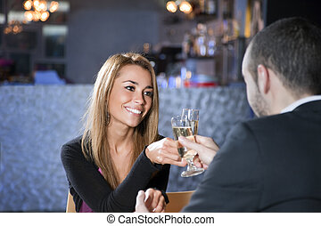 toast - mid adult couple toasting in restaurant. Copy space