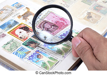hand with magnifying glass and stamp album