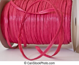 Big Spool of Pink Raffia Ribbon - This closeup is a roll of...