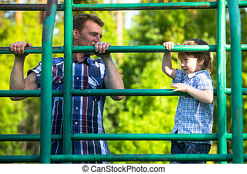 Father and son playing on the park playground.