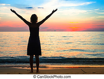 A young woman on the beach meets a beautiful sunset.