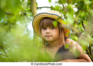 Little lovely girl posing in a straw hat in the park.