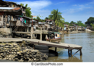 Asian slums on river bank - Asian slums, poor houses with...