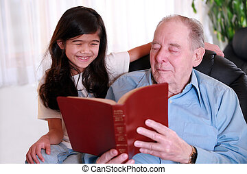 Elderly man and little girl reading Bible together, great...