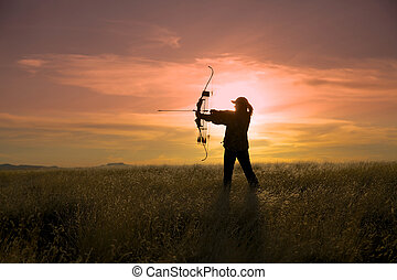 Bowhunter at Sunset - a bow hunter silhouetted at sunset
