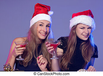 Girlfriends in Christmas hats with cocktails