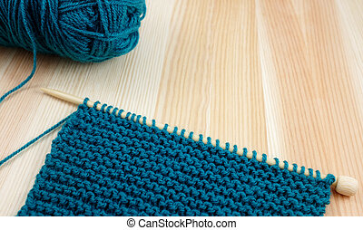 Garter stitch on knitting needle with teal yarn - Garter...