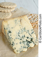 Stilton cheese on aged parchment paper with oat biscuits and...