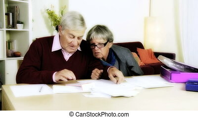 Elderly couple calculating bills - Unhappy angry old couple...