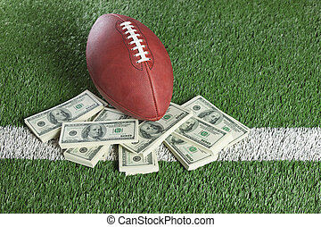 NFL football on field with a pile of money - An NFL football...
