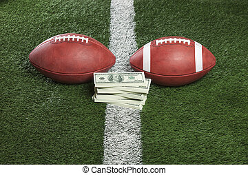 Pro and college style footballs with money between - Pro and...