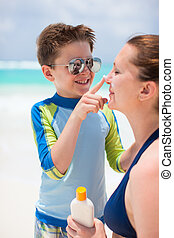 Sun protection - Little boy applying sun cream to her mother...