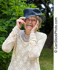 Laughing elderly lady wearing a hat - Portrait of a lively...