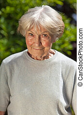 Kindly elderly lady standing in her garden looking at the...