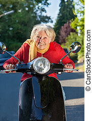 Elderly lady having fun on her scooter crouching low of the...