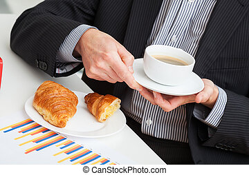Cup of coffee and croissant at work