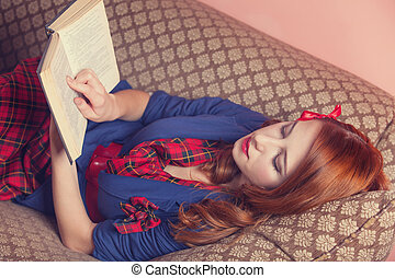 Women in 70s style reading book on the sofa