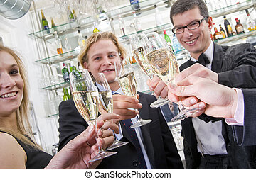 a toast on new years eve - several people toasting with...