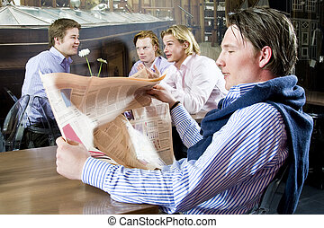 reading a newspaper - a young male reading his newspaper in...