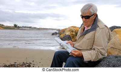 Old man relaxing on beach