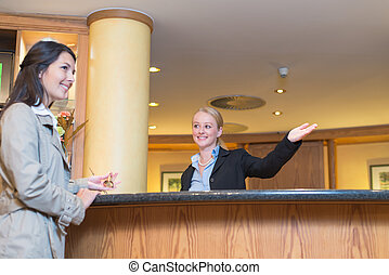 Smiling receptionist helping a hotel guest - Low angle view...