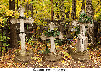 Three graves with crosses rickety and wreaths at the...
