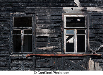 Facade of a wooden house, burnt in the fire